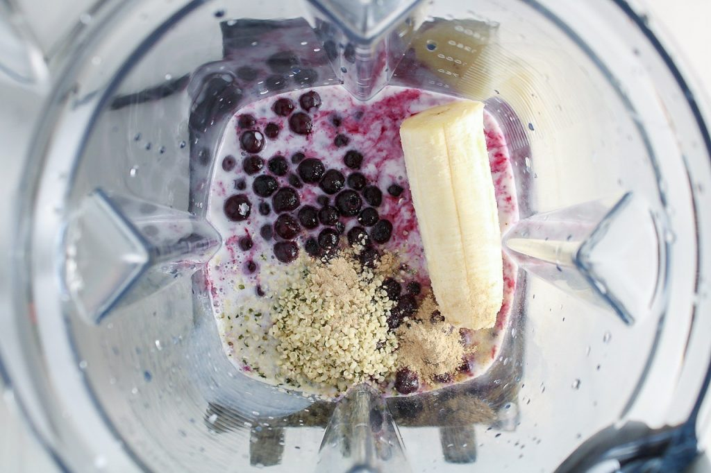 n process picture: Showing inside of a blender that contains banana, vegan milk, seeds and frozen fruits.