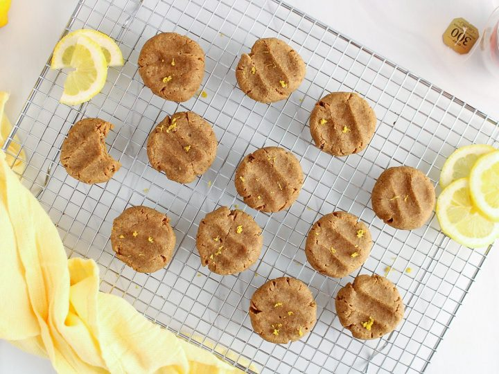 There are a few vegan lemon cookies that are cooling down on a cooling rack. The cookies are sprinkled with lemon zest. There are slices of lemon around the cookies as well as a cup of tea and a yellow hand towel.