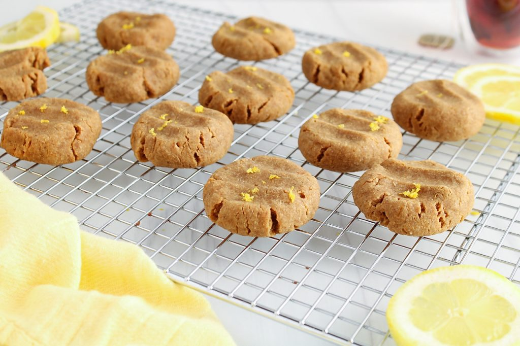Front view on a cooling rack that has a few vegan lemon cookies on top. The cookies are topped with lemon zest and there are a few lemon slices on the side. You can also see a cup of tea in the background.