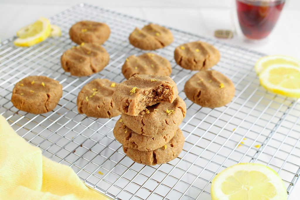 Showing are 4 vegan lemon cookies pilled on top of each other. The very top one has one bite taken off and has a sprinkle of lemon zest. There are more cookies in the background as well as lemon slices and a cup of tea and a yellow hand towel.