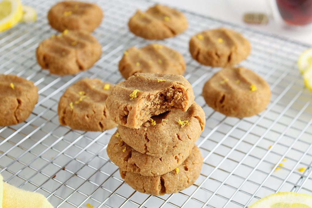 Showing are 4 vegan lemon cookies pilled on top of each other. The very top one has one bite taken off and has a sprinkle of lemon zest. There are more cookies in the background as well as lemon slices and a cup of tea.