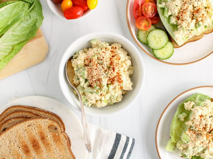 Showing is a small white bowl that contains a vegan eggless salad topped with paprika. The bowl is surrounded with tomatoes, lettuce, toasted bread and open sandwiches made with the salad.