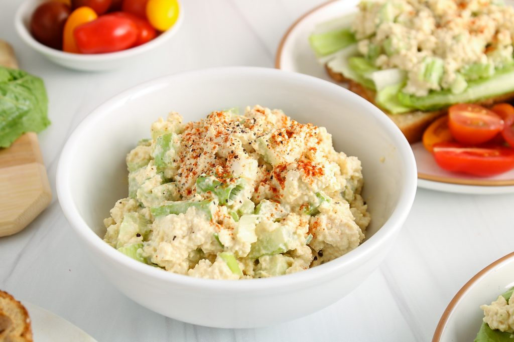 Front angle view on a white bowl filled with a homemade eggless salad that's topped with paprika and black pepper. You can some fresh produce like tomatoes and romaine lettuce in the background to make a sandwich with the eggless salad.