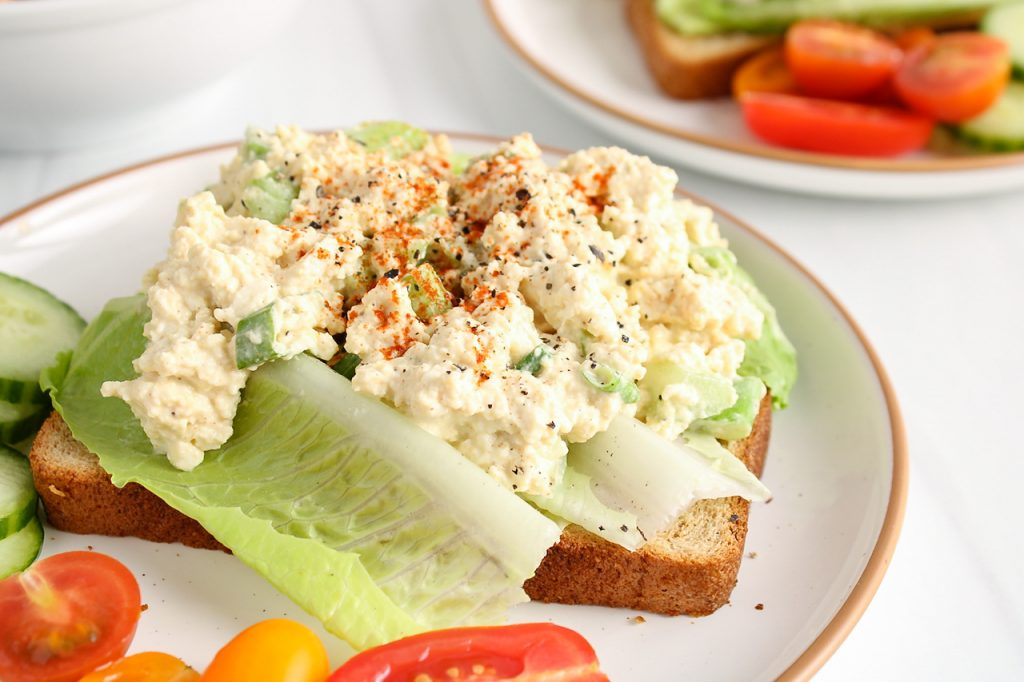 Front angle view on a toast that's topped with romaine lettuce and a vegan eggless salad. The open sandwich has a sprinkle of paprika and black pepper. There are sliced cucumber and tomatoes around the open sandwich.