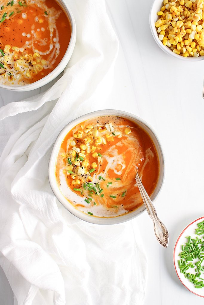 There are 2 white bowls that contain a butternut squash and red pepper soup that's topped with coconut milk, corn, chives and black pepper. There are a few bowls around containing more of the toppings.