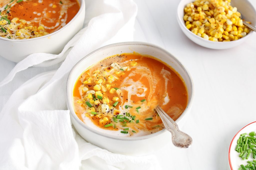 Front angle view on 2 white bowls that contain a butternut squash and red pepper soup that's topped with coconut milk, corn, chives and black pepper. There are a few bowls around containing more of the toppings.