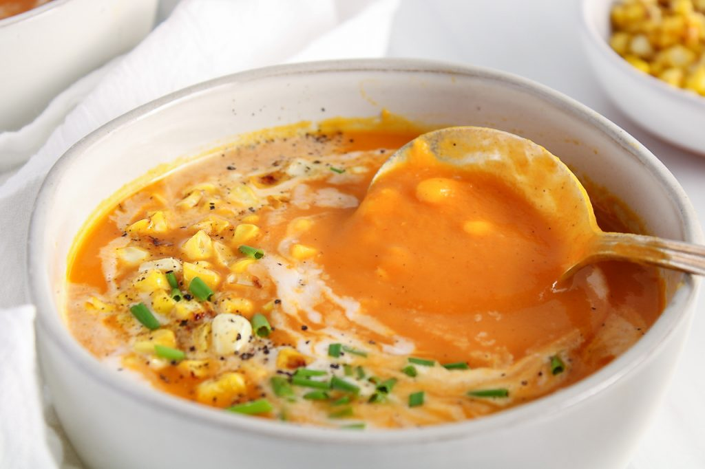 Close up on a white bowl containing a butternut squash and red pepper soup that's topped with corn, coconut milk and chives. There is a spoon in the bowl that's taking some of the soup.