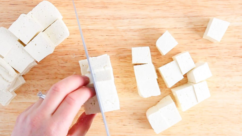 You can see a hand holding a knife while cutting a bloc of tofu that's on a wooden board.