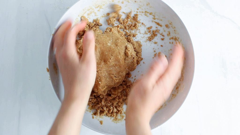 In process picture: there are 2 hands pressing on the dough to form a large ball.