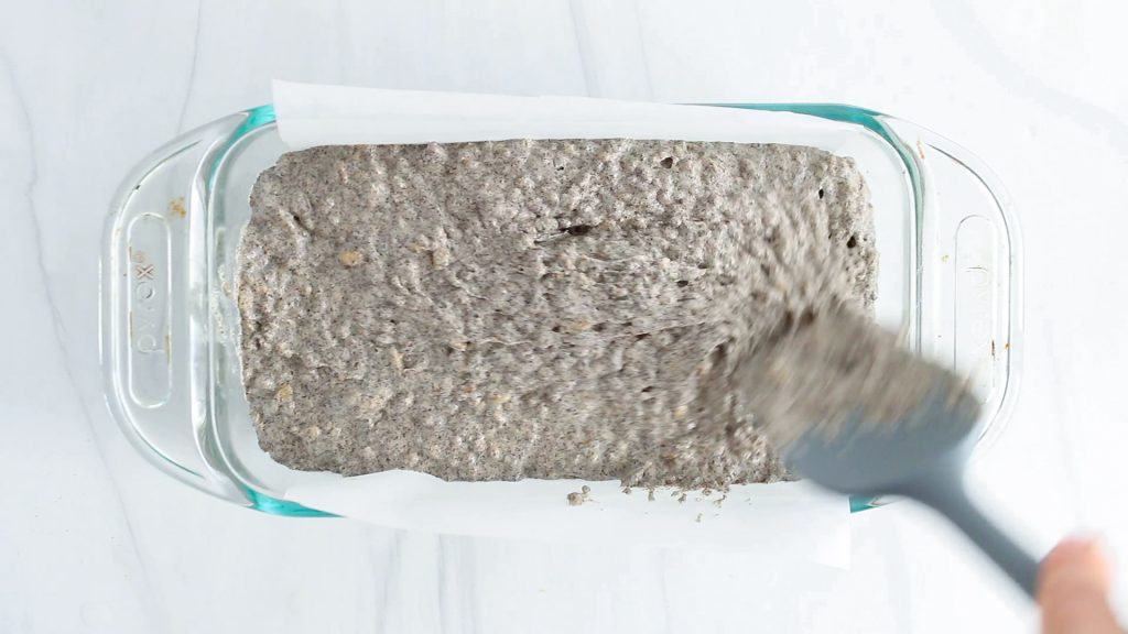 There is a glass loaf pan with a dark mixture being evenly distributed inside.