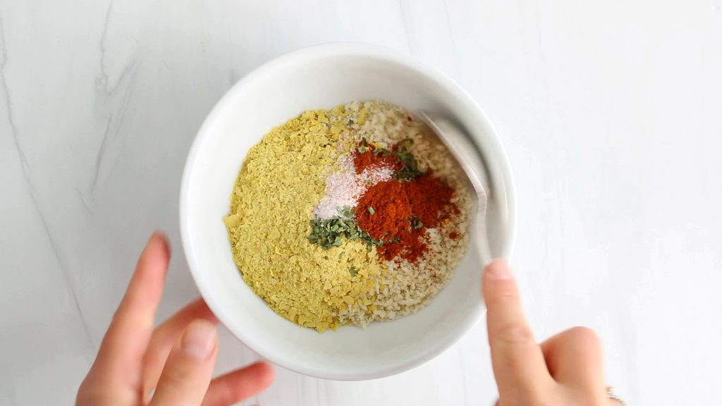 In process picture: you can see someone holding on a spoon while stirring in a small bowl containing panko breadcrumbs, paprika, salt, dried parsley and pepper.