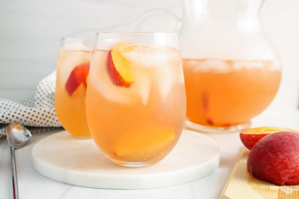 Showing is a glass of Oolong peach iced tea that's filled with ice cubes and slices of peach. There is a large pitcher in the background with more of the tea as well as a second glass with some of the tea. There are pieces of peach on the side and a black and white with dots hand towel on the side.