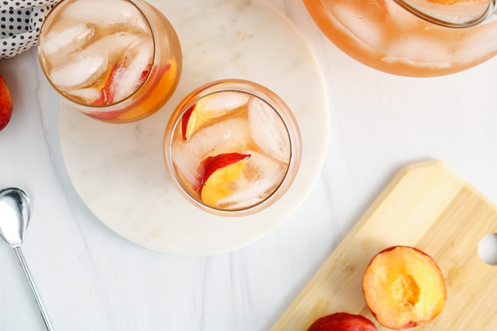 Overhead view on 2 glasses of oolong peach iced tea that are filled with ice cubes and slices of peach. There is a large pitcher with more of the tea on the side.