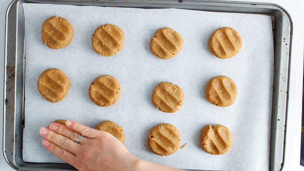 In process picture: There are a few cookies on a baking sheet and you can see a hand pressing on them to shape them in a disc.