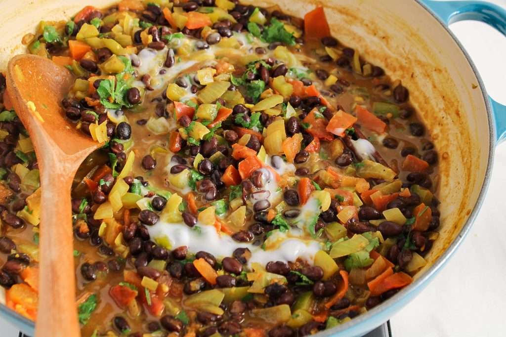 Close up on a creamy black bean curry that's cooking in a large pan. You can see a drizzle of coconut yogurt on top as well as a wooden spoon.