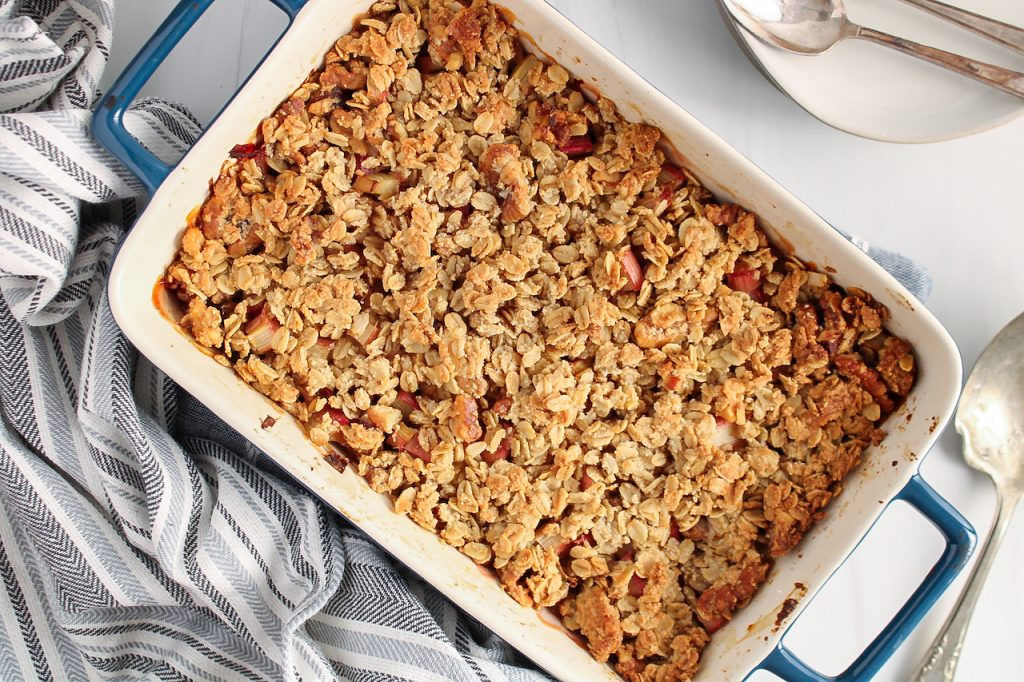 Overhead view on a rectangular baking dish that contains a vegan rhubarb crumble. There is a blue and grey hand towel on the side as well as serving plate and spoon.