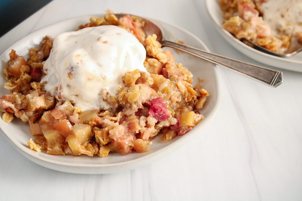 Close up on a vegan rhubarb crisp topped with ice cream on a small plate. There is a spoon on the side of the plate.