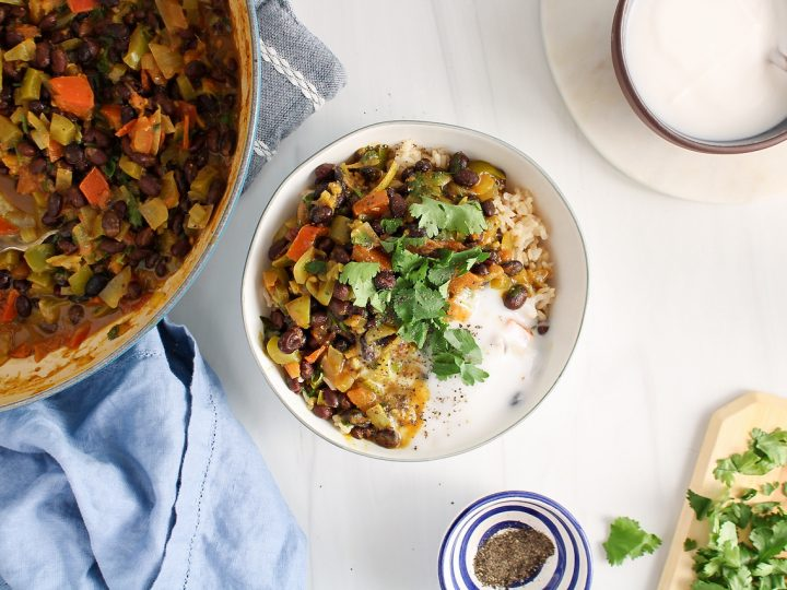 Overhead view on a small white bowl that contains brown rice that's topped with a creamy black bean curry. The dish is also garnished with coconut yogurt and fresh cilantro. You can see more cilantro, black pepper and yogurt in bowls on the table.