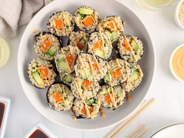 Showing are many sweet potato sushi rolls that are pilled on a large white plate and drizzled with a spicy vegan mayo sauce. Beside on the table, you can see small bowls containing sesame seeds, soy sauce, spicy mayo and a few glasses of white wine. There are plate, chop stick and a beige hand towel as well.