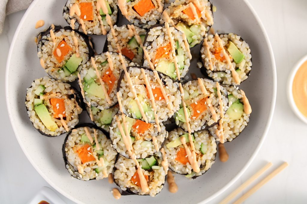 Close up on a few sweet potato sushi rolls pilled on a large white plate. The vegan maki are topped with sesame seeds and a drizzle of spicy mayo sauce.