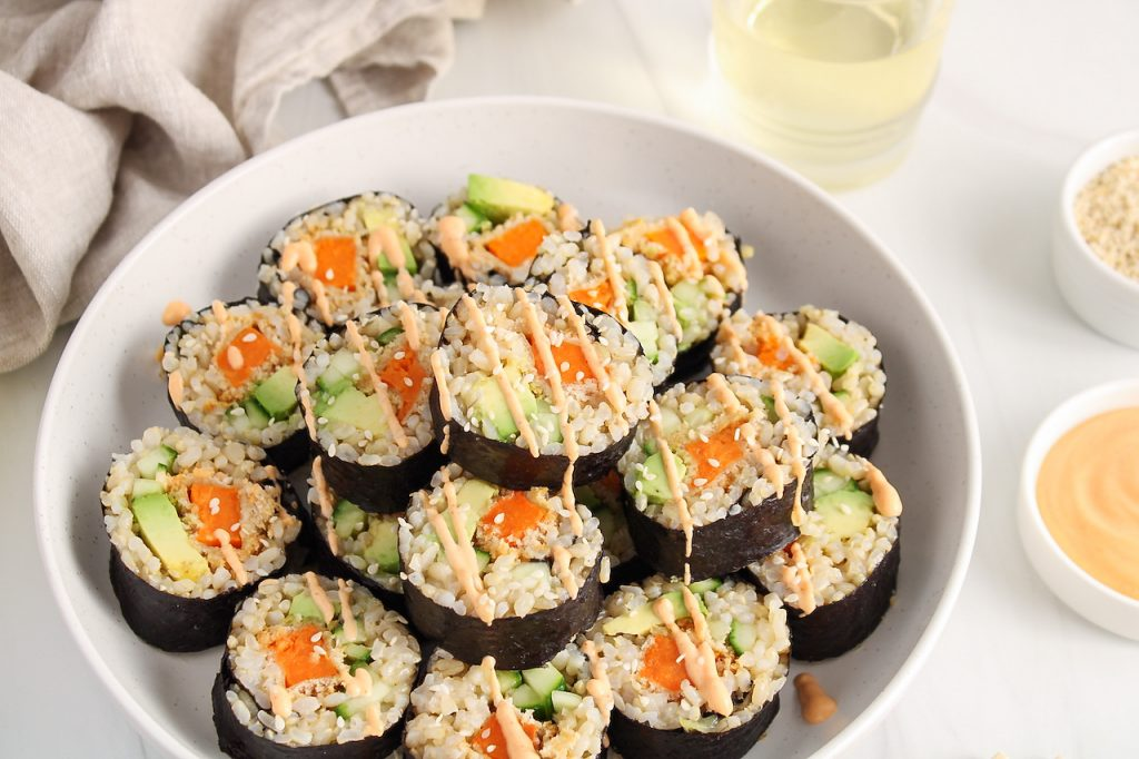 Angle view on sweet potato sushi rolls that are placed on a large white plate then drizzled with spicy mayo and sprinkled with sesame seeds.