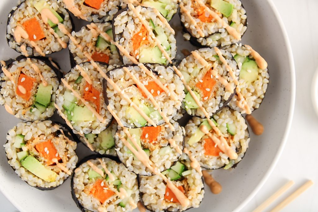 Overhead view on a close up of a vegan brown rice and crispy sweet potato sushi rolls that's placed over many other sushi.
