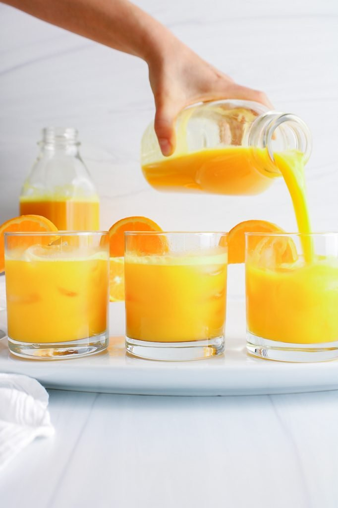 There are 3 short glasses containing a ginger turmeric glowing shot. The glasses are on a large white plate and you can see someone pouring some of the turmeric juice in the third glass. There is also a larger container with more of the juice in the background.