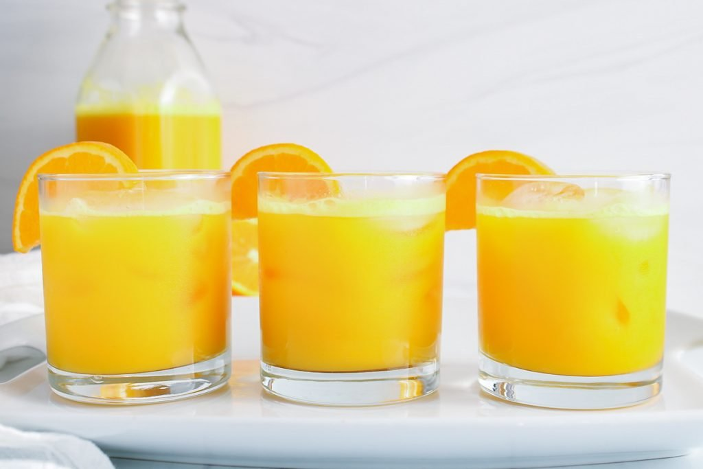 Showing are 3 glasses containing ginger turmeric shots with a slice of orange on the side of the glass. There is another large juice container in the background.