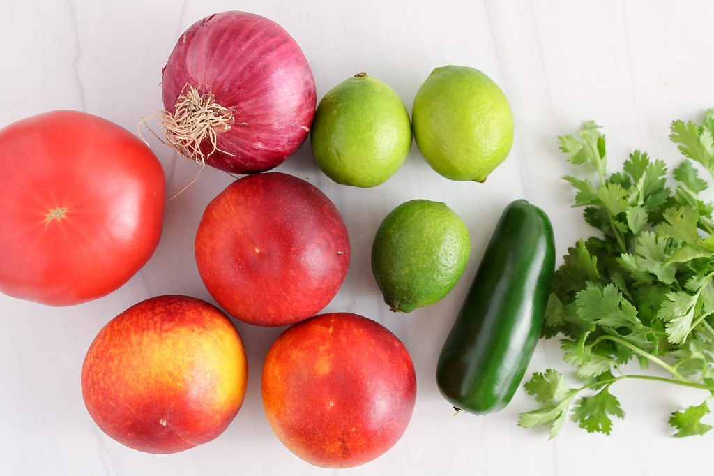 Showing are the ingredients needed to make this recipe: fresh peaches, limes, jalapeño cilantro and red onion.