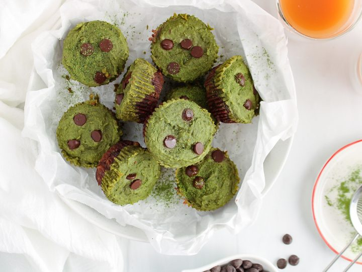 Showing is an overhead view on a few mini matcha brownies that are pilled in a shallow large bowl that was previously covered with some parchment paper. The brownie are layer with a bottom dark chocolate brownie and topped with a bright green match layer. The cups are also topped with a few chocolate chips. Beside, you can see 2 cups of tea, some more chocolate chips in a bowl and a mini sifter that's on a plate that also contains some matcha powder.