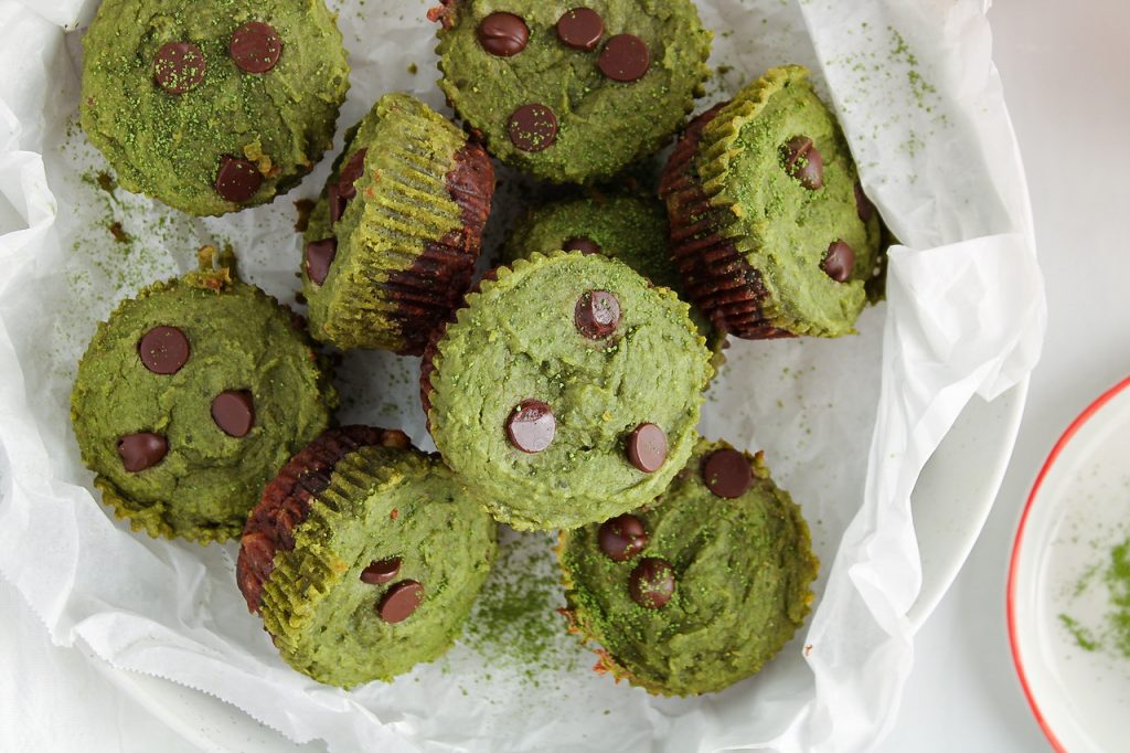Showing is an overhead view on a few mini matcha brownies that are pilled in a shallow large bowl that was previously covered with some parchment paper. The brownies are layered with a bottom dark chocolate brownie and topped with a bright green match layer. The cups are also topped with a few chocolate chips. Beside, you can see a mini sifter that's on a plate that also contains some matcha powder.