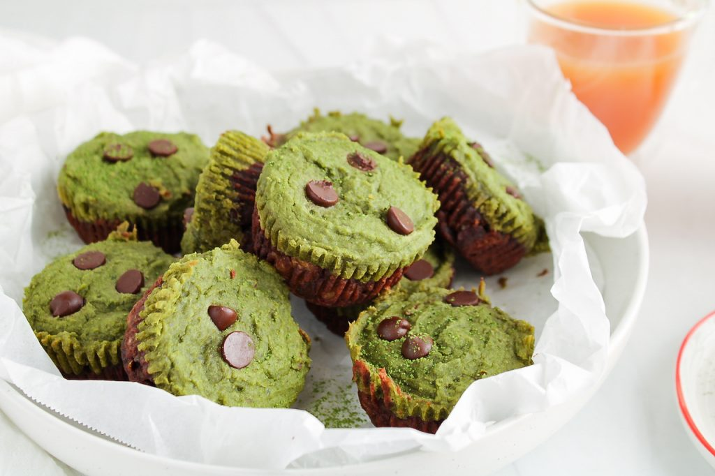 Front angle view on a few mini matcha cups that are pilled in a large white bowl that was also first covered with white parchment paper. You can see that the mini cups are layered with a bottom dark chocolate classic brownies then topped with a bright green matcha brownie topping. The cups are also topped with a few chocolate chips. There is a cup of tea in the background.