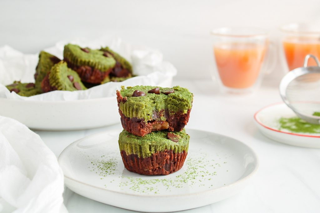 Front view on 2 mini matcha brownies that are pilled on top of each other. You can nicely see their bottom dark layer and top bright green layer. These 2 brownies are on a white plate and the top mini brownie has a bite taken off. You can see more of them in a bowl in the background. Also in the background, there are 2 cups of tea and a matcha sifter with some powder inside that's on a plate.