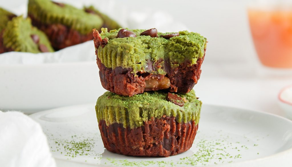 Close up on 2 mini matcha brownies that are pilled on top of each other with a bite taken off on the top brownies.