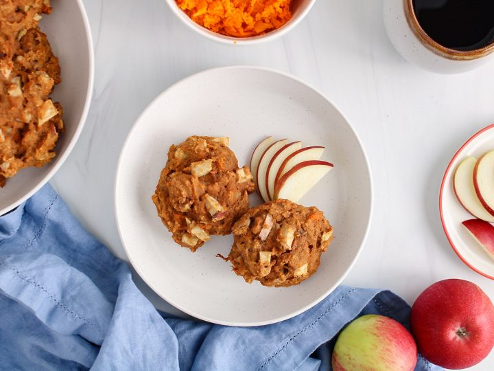 Over head view on a white plate that contains 2 sweet potato breakfast cookies and a few slices of apple on the side. Beside the plate, you can also see more cookies in a larger plate, a blue hand towel, fresh apples, a cup of coffee and a bowl with some mashed sweet potatoes.