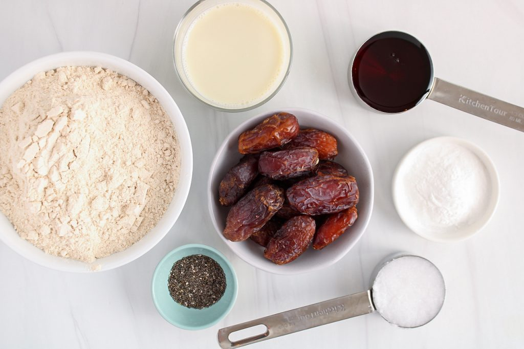 Showing are the ingredients needed to make date scones. You can see a few bowls containing fresh medjool dates, flour, vegan milk, coconut oil, chia seeds, baking powder and maple syrup.