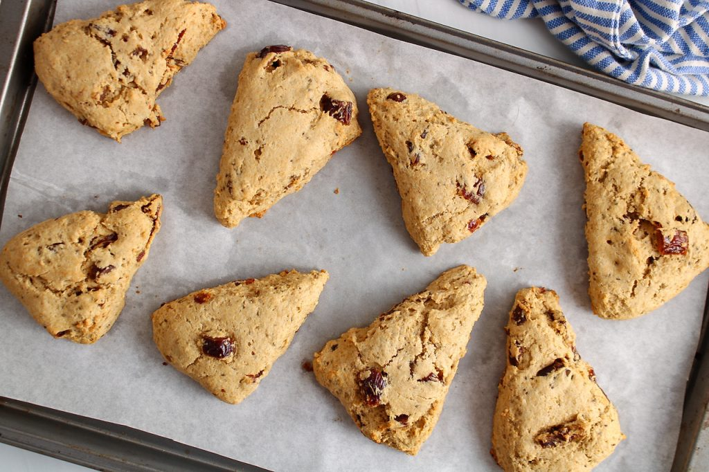 Overhead view on a baking sheet that contains 8 vegan date scones.