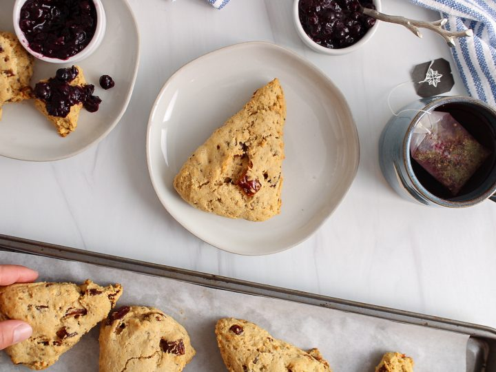 Showing is an overhead view on a date scone that's on a small plate. Surrounding the plate, there is the baking sheet with more of the scone still on it with a small container filled with a blueberry jam, a cup of tea and a white and blue hand towel.