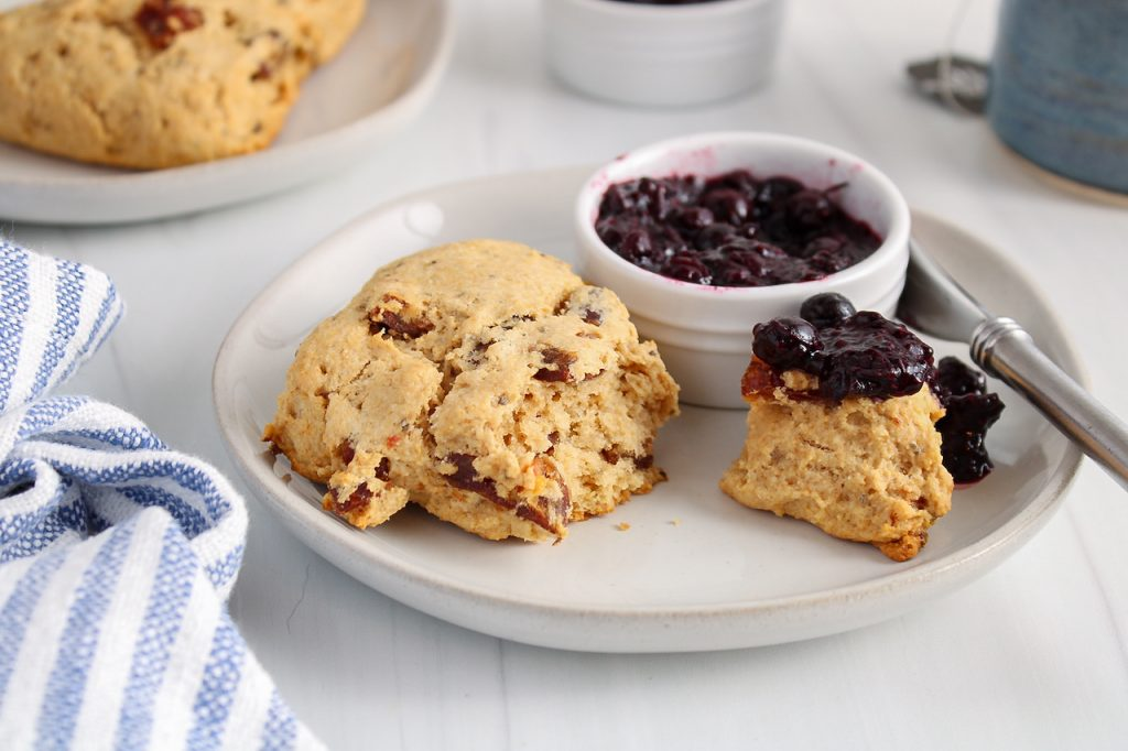 Showing is a date scone on a plate that was just cut in half to show the middle tender texture. One half is topped with a blueberry jam and there is a small bowl with more of the jam on the plate as well.