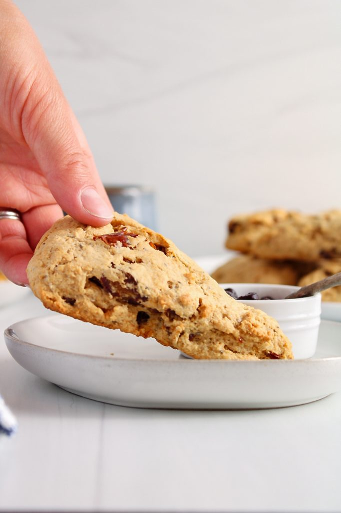 There is a hand transferring a date scone on a plate. You can see a small bowl with some jam and there are more scones in the background as well.