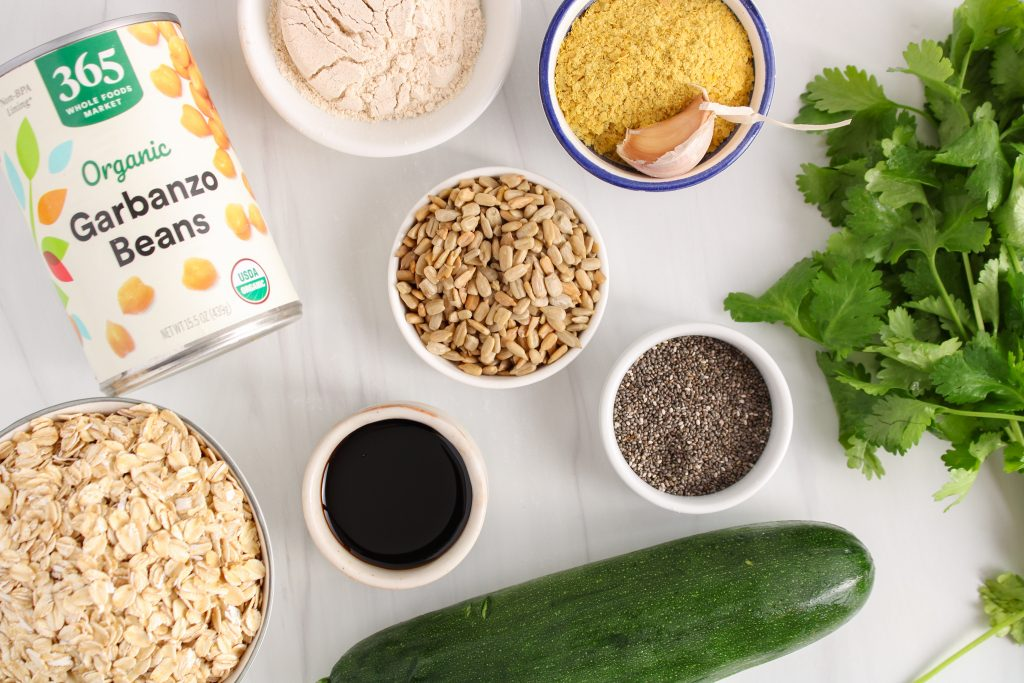 Showing are the ingredients needed to make this recipe, you can see a can of chickpea, rolled oats, a zucchini, sunflower seeds, nutritional yeast, garlic, chia seeds, soy sauce, flour and fresh herbs.