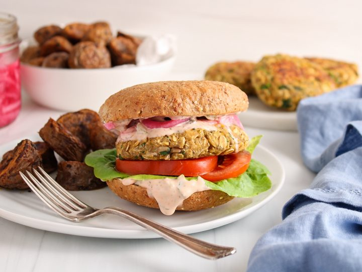 Showing is a vegan chickpea and oat burger that's on a plate with a side of roasted potatoes. The burger also layers tomatoes, lettuce, a pinkish sauce and pickled red onions. You can see more roasted potatoes and burger patties in the background, a jar with some more pickled onions as well as a blue hand towel.
