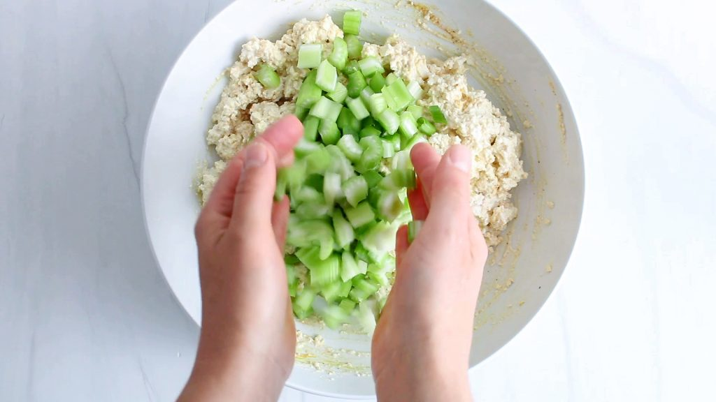 In process picture: you can see 2 hands adding chopped celery to a bowl containing a creamy tofu mixture.