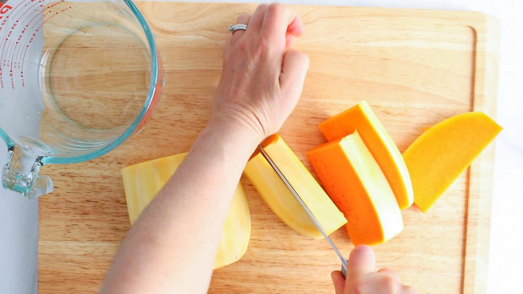 In process picture: There is a half butternut squash being cut with a large knife.