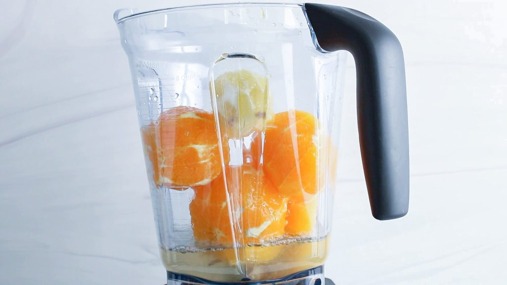 In process picture: front view on a blender that contains whole and peeled oranges and lemon.