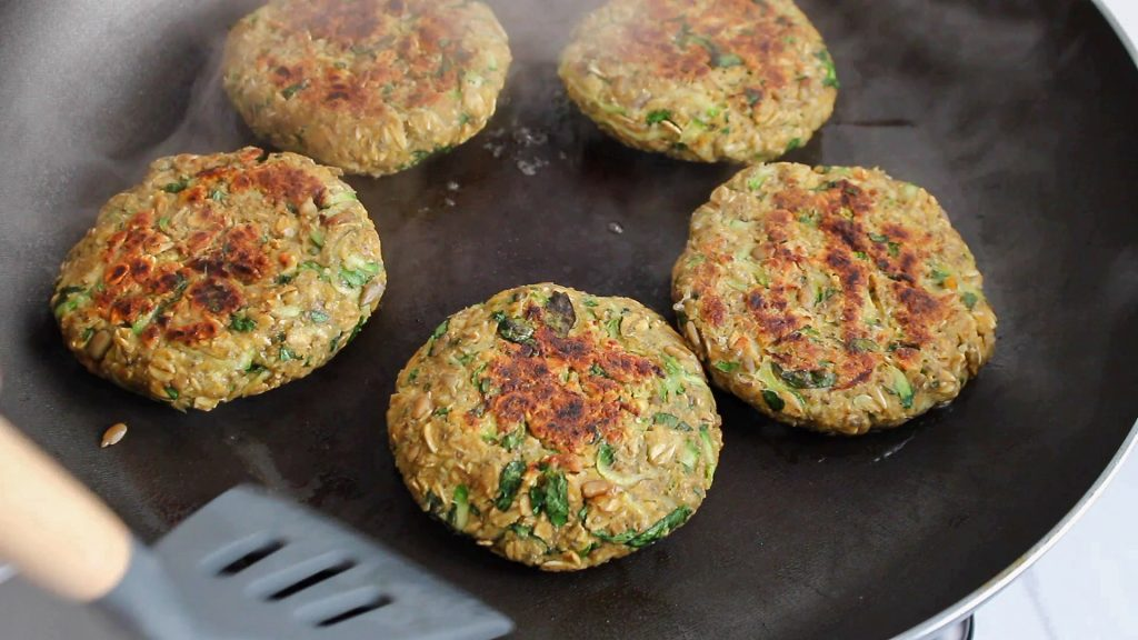 In process picture: you can see a bean patties cooking in a non stick pan with a spatula flipping them.