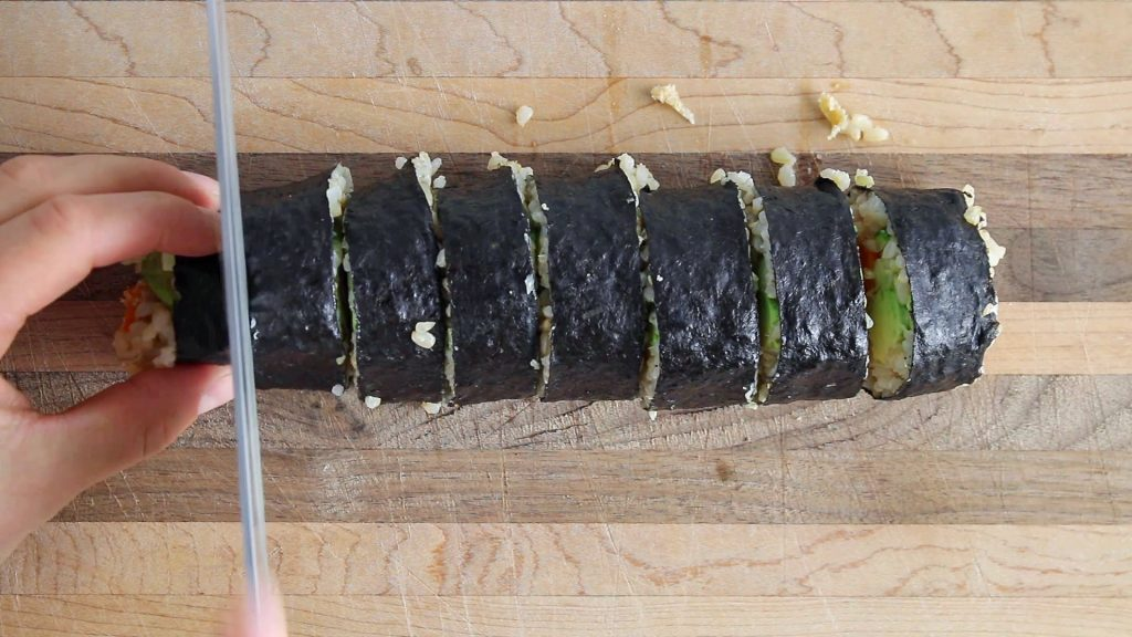 In process picture: you can see 2 hands that are cutting a sushi roll into maki