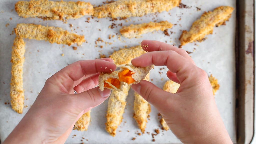 In process picture: you can see 2 hands that are cutting in 2 pieces a long sweet potato stick covered with a panko breading.
