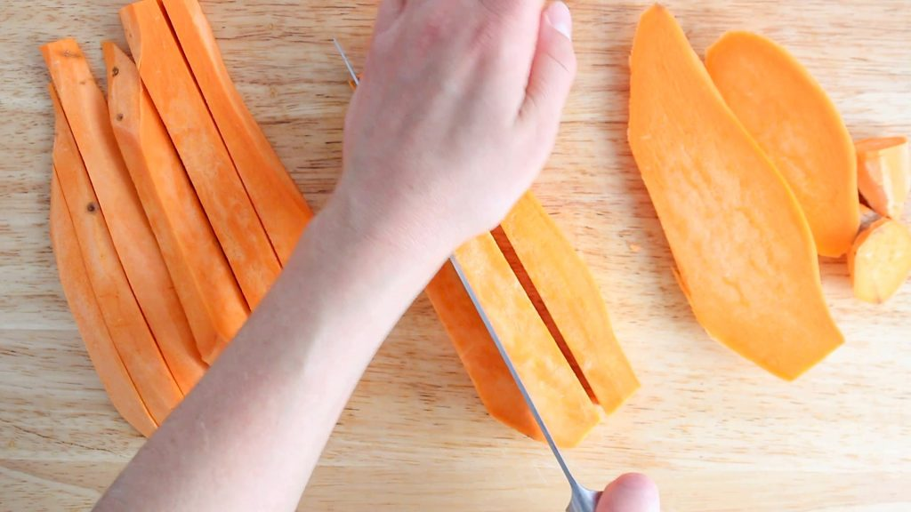 In process picture: there are sweet potato that are being cut into the shape of a stick on a wooden board