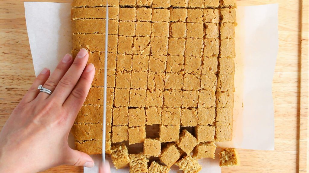 In process picture: you can see 2 hands and a large knife that's cutting a square cake into smaller squares.